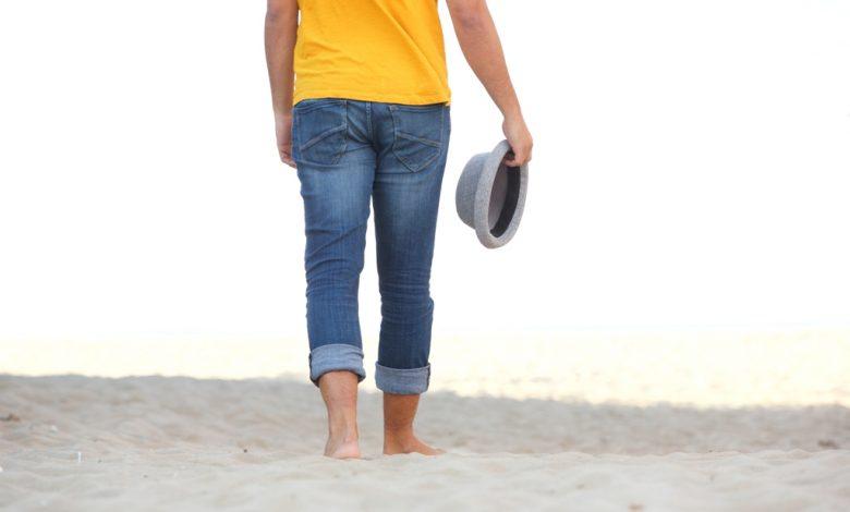 разхождащ се мън по плажа с боси крата